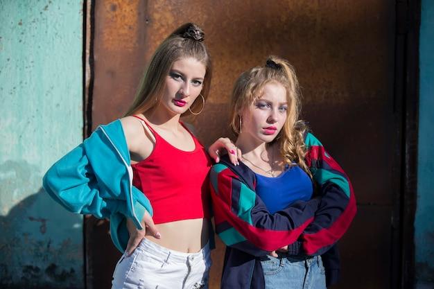 Due ragazze divertenti in abiti luminosi nello stile degli anni novanta