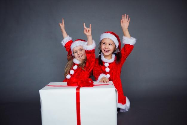 Due ragazze divertenti in cappelli e vestiti di babbo natale che si divertono con una grande scatola regalo nastro rosso