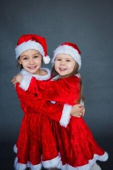 Due ragazze divertenti in cappelli e vestiti di babbo natale che si divertono