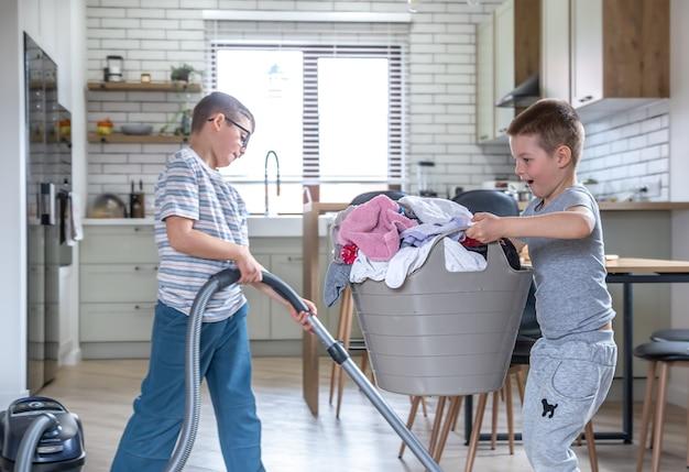 Due fratellini divertenti aiutano con i lavori domestici, aspirano e aiutano la mamma con il bucato.