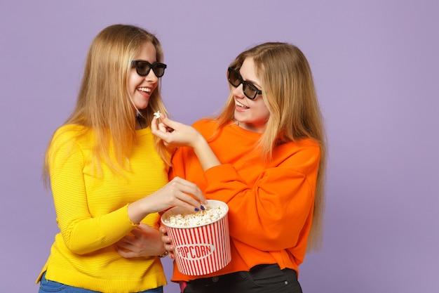 Due giovani sorelle gemelle bionde divertenti ragazze in occhiali 3d imax che guardano film, tenendo popcorn isolato sulla parete blu viola pastello. concetto di stile di vita familiare di persone.