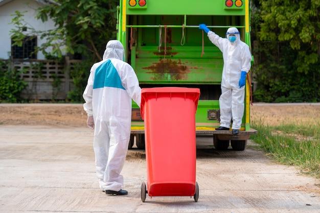 Due uomini dell'immondizia in indumenti protettivi dpi dpi indossano guanti di gomma medica che lavorano insieme per svuotare le pattumiere per la rimozione dei rifiuti con i rifiuti di carico del camion e il cestino, malattia di coronavirus 2019.