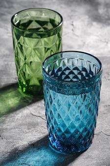 Due tazze di vetro geometriche con acqua nei colori blu e verdi con raggi di luce ombra colorata su cemento di pietra, angolo di visione