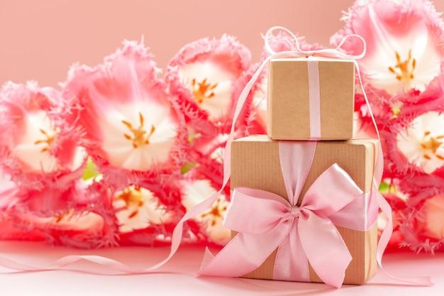 Contenitore di regalo due avvolto con carta artigianale e fiocco rosa su sfondo di fiori rosa.