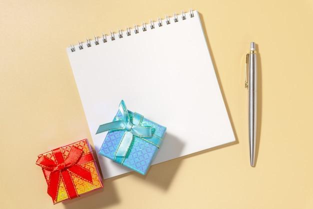 Due scatole regalo con un fiocco e un blocco note con una penna su uno sfondo pastello.