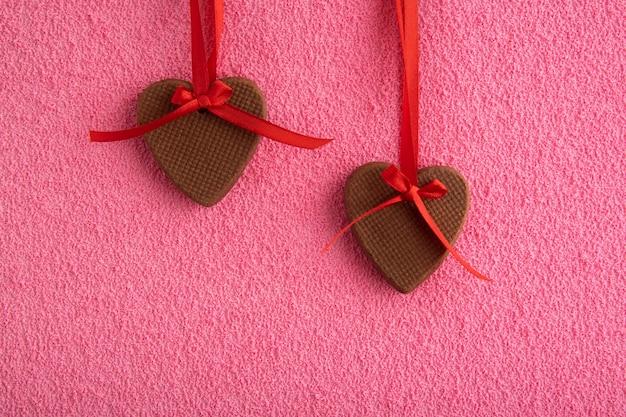 Due biscotti di panpepato a forma di cuori su nastri rossi su sfondo rosa. festa della mamma. giornata della donna. san valentino.