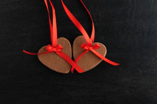 Due biscotti del cuore del pan di zenzero sui nastri rossi su fondo nero. festa della mamma. giornata della donna. san valentino.