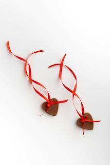 Due cuori di panpepato il giorno di san valentino con nastro rosso su sfondo bianco. cornice verticale.