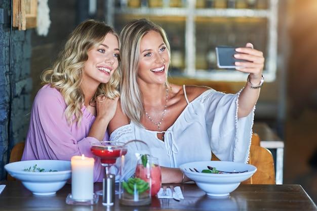 Due amiche che pranzano al ristorante e usano lo smartphone