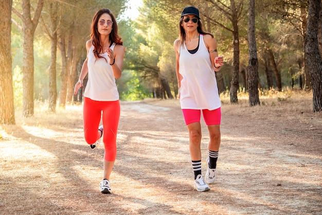 Due amiche che corrono insieme in una foresta al tramonto