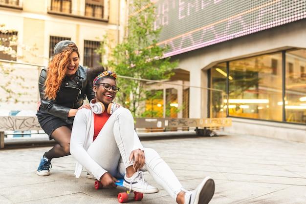 Due ragazze che usando skateboard e divertendosi.