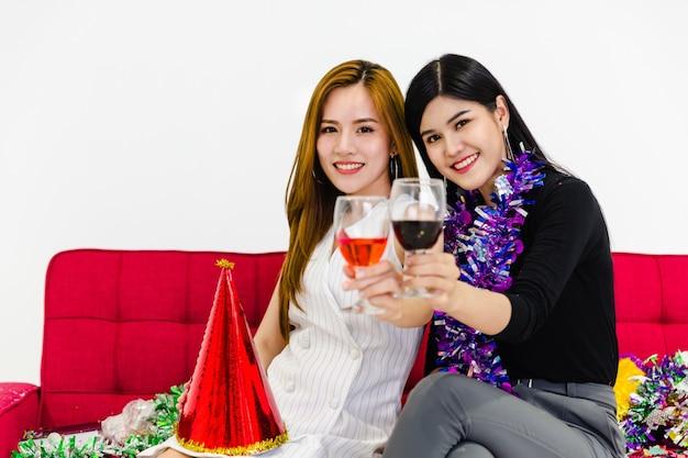 Concetto della festa pranzante del vino di vetro della tenuta di due ragazze
