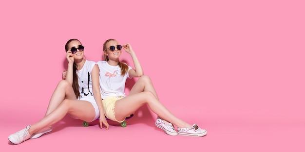 Due pattinatrici impazziscono e si divertono insieme. belle donne sportive, emozione positiva. sfondo rosa.