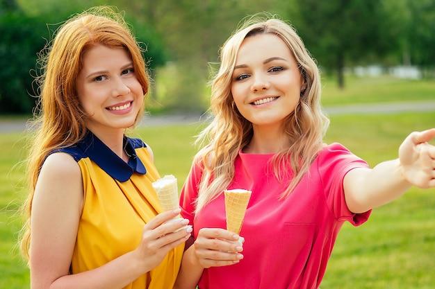 Due amiche bella giovane donna rossa allo zenzero in un vestito giallo e bionda persona di sesso femminile in un vestito rosa che mangia gelato alla vaniglia in un cono di cialda, nel parco estivo scattare foto selfie telefono.