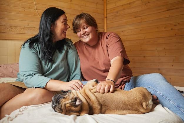 Due amiche si prendono cura del loro animale domestico durante il loro tempo libero in camera da letto