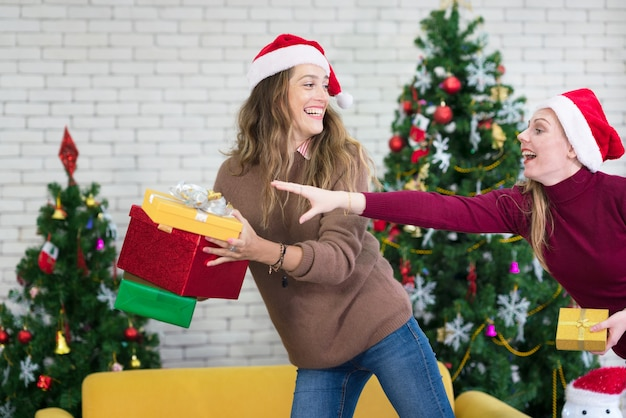 Due amiche che ridono e che condividono i regali di natale. celebrazione di natale e festa di capodanno