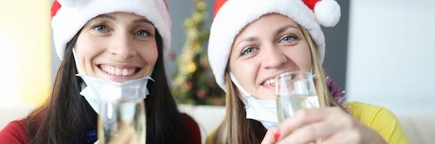Due amiche in cappelli di babbo natale in maschere mediche protettive tengono bicchieri di champagne