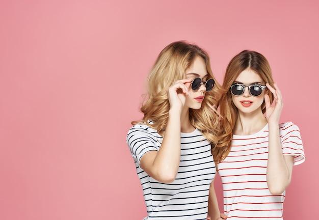 Due amiche stanno fianco a fianco in magliette a righe occhiali moda estate sfondo rosa