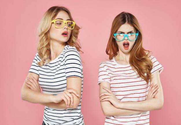 Magliette a righe di due amiche con sfondo rosa di occhiali da sole
