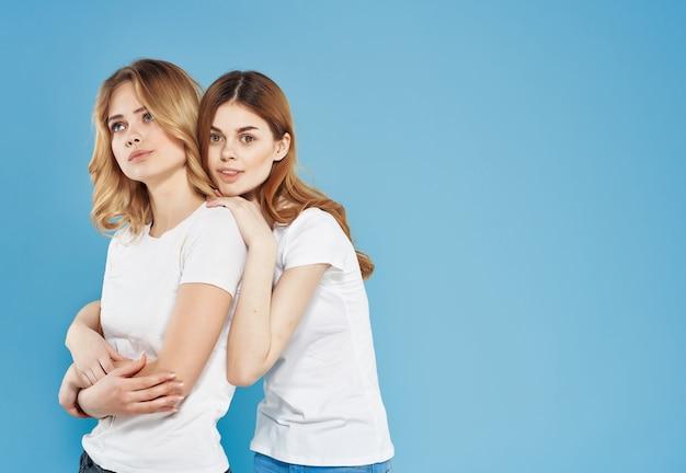 Due amiche in magliette bianche abbracciano emozioni divertenti amicizia in stile moderno. foto di alta qualità