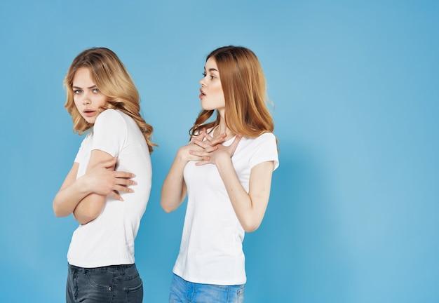 Due amiche in magliette bianche abbracciano emozioni divertenti in stile moderno amicizia