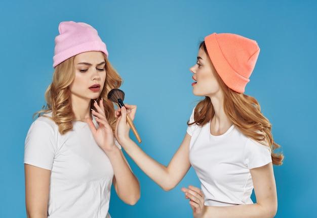 Due amiche in magliette bianche truccano l'amicizia aiutano con i cosmetici