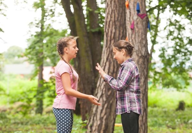 Due ragazze stanno giocando con le mani applaudendo il gioco all'aperto, l'amicizia degli adolescenti