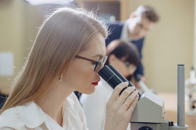 Due ragazze e un ragazzo lavorano con i microscopi