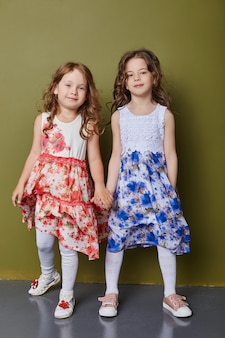 Due ragazze in abiti primaverili luminosi su uno sfondo color oliva