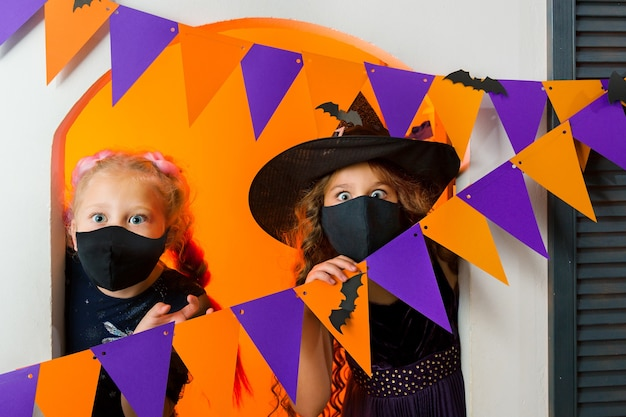Due ragazze in costumi di carnevale guardano con sorpresa la telecamera da dietro una ghirlanda di bandiere