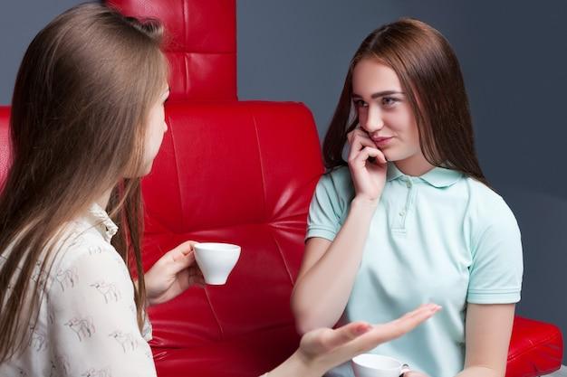 Due ragazze che bevono caffè e spettegolano insieme