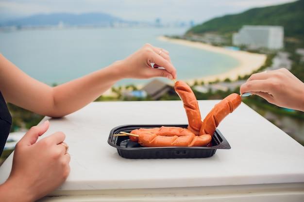 Due ragazze mangiano salsicce sullo sfondo del mare
