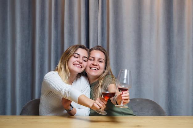 Due ragazze di aspetto europeo con i capelli biondi sono sedute al tavolo, bevono vino e ridono, si rilassano a casa, alcol