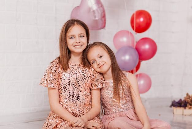 Due ragazze in abiti fantasiosi in uno studio luminoso con palloncini