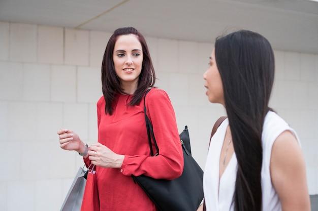 Due amiche che fanno shopping donne che comprano e parlano caucasica una ragazza asiatica che cammina