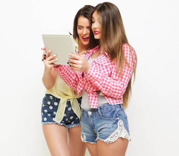 Due amiche che prendono selfie con tavoletta digitale su sfondo bianco
