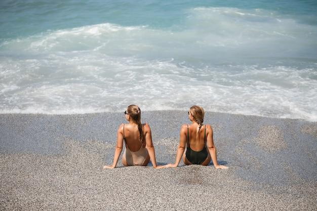 La ragazza di due ragazze è seduta sulla riva sabbiosa del mare e le onde le hanno inzuppate in costumi da bagno in una giornata calda e soleggiata