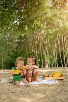 Due ragazze fanno un picnic su una spiaggia sabbiosa e mangiano angurie gialle e focacce