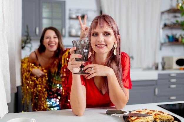Due ragazze si divertono in cucina dopo una festa