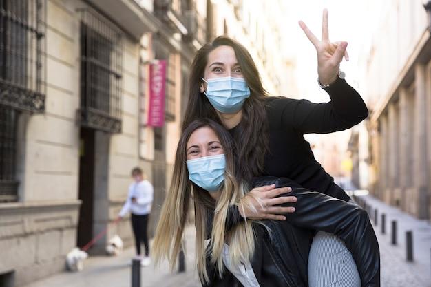 Due ragazze che si divertono per strada. indossano maschere mediche.