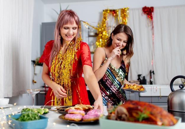 Due ragazze si divertono con le ciambelle in cucina dopo una festa
