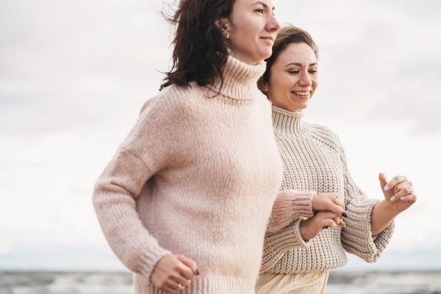 Due ragazze si tengono per mano e corrono lungo la riva del mare le sorelle si divertono insieme