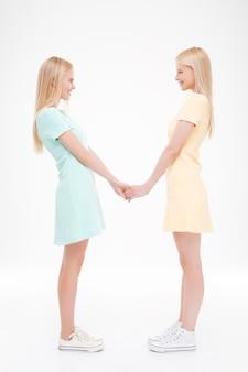 Due ragazze che si tengono per mano. isolato sopra il muro bianco.
