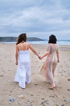 Due ragazze che si tengono per mano coppie delle signore sulla spiaggia