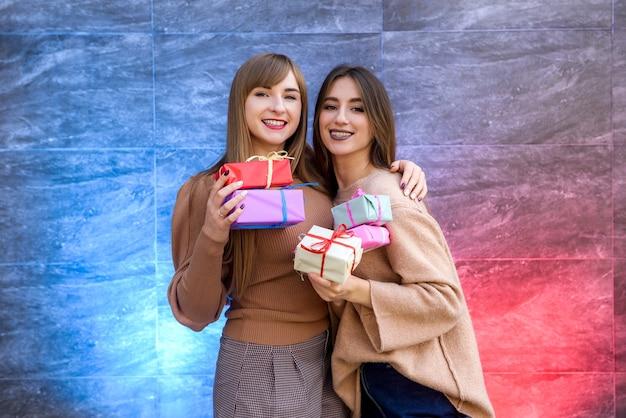 Due ragazze in possesso di confezione regalo. celebrazione del nuovo anno o natale o compleanno. fare un regalo