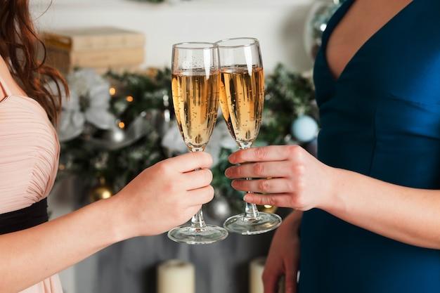 Due ragazze che tengono i vetri di champagne. festeggia il nuovo anno, natale. accanto all'albero di natale