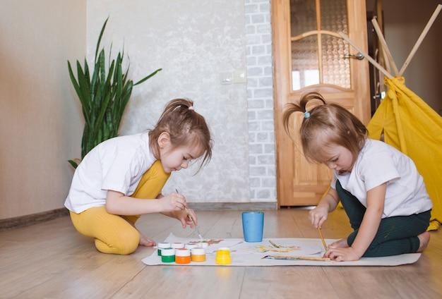 Due ragazze in abiti chiari si siedono per terra in ginocchio e disegnano con entusiasmo con acquerelli luminosi.