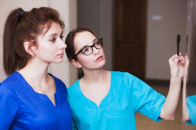 Due infermiere stanno studiando gli strumenti chirurgici. educazione medica