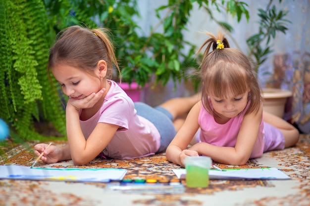 Due ragazze dipingono con vernici stese sul pavimento a casa o all'asilo