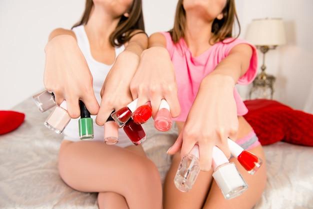 Due ragazze in pigiama tenendo le vernici